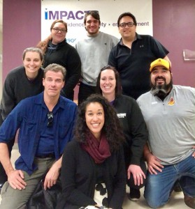 (Front Row: IMPACT Boston Program Coordinator Adriana Li; Middle Row kneeling, from left to right: IMPACT Boston Trainer & Instructor Mike Perry, Turtle Mountain IMPACT Instructor Sara Davis, Turtle Mountain IMPACT Suited Instructor Wes Davis; Back Row, standing, from left to right: IMPACT Boston Director Meg Stone, Turtle Mountain IMPACT Director Shanda Poitra, IMPACT Boston Program Coordinator Ben Comeau, Turtle Mountain IMPACT Suited Instructor James Decoteau)